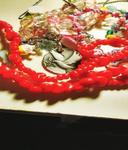 Plastic necklaces and a dove pendant mixed together: a metaphor for mothers in ministry.
